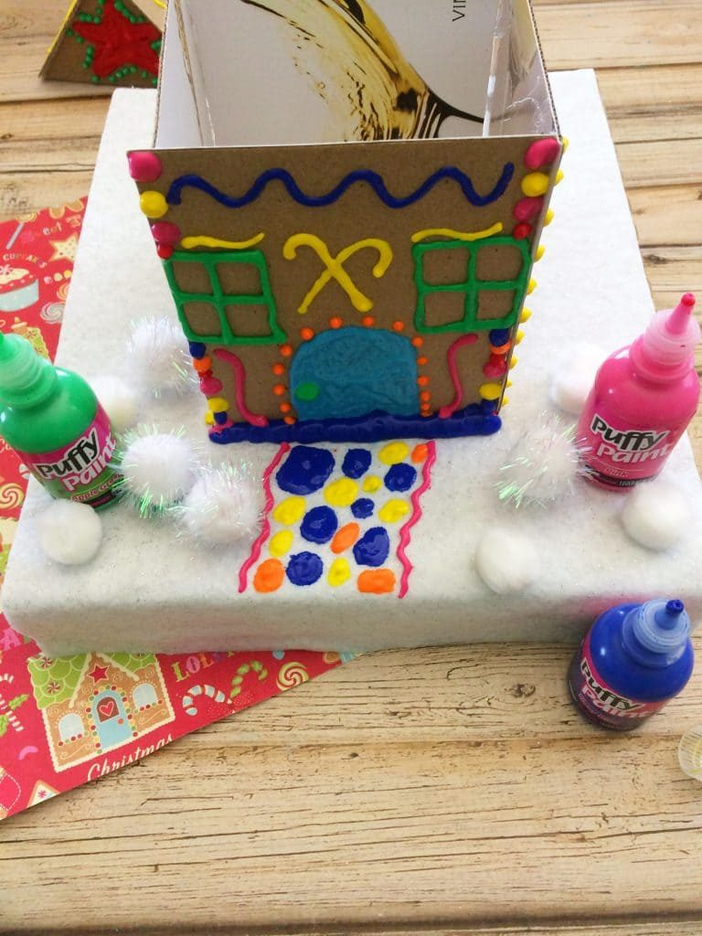 Decorate your cardboard gingerbread house with puffy paint
